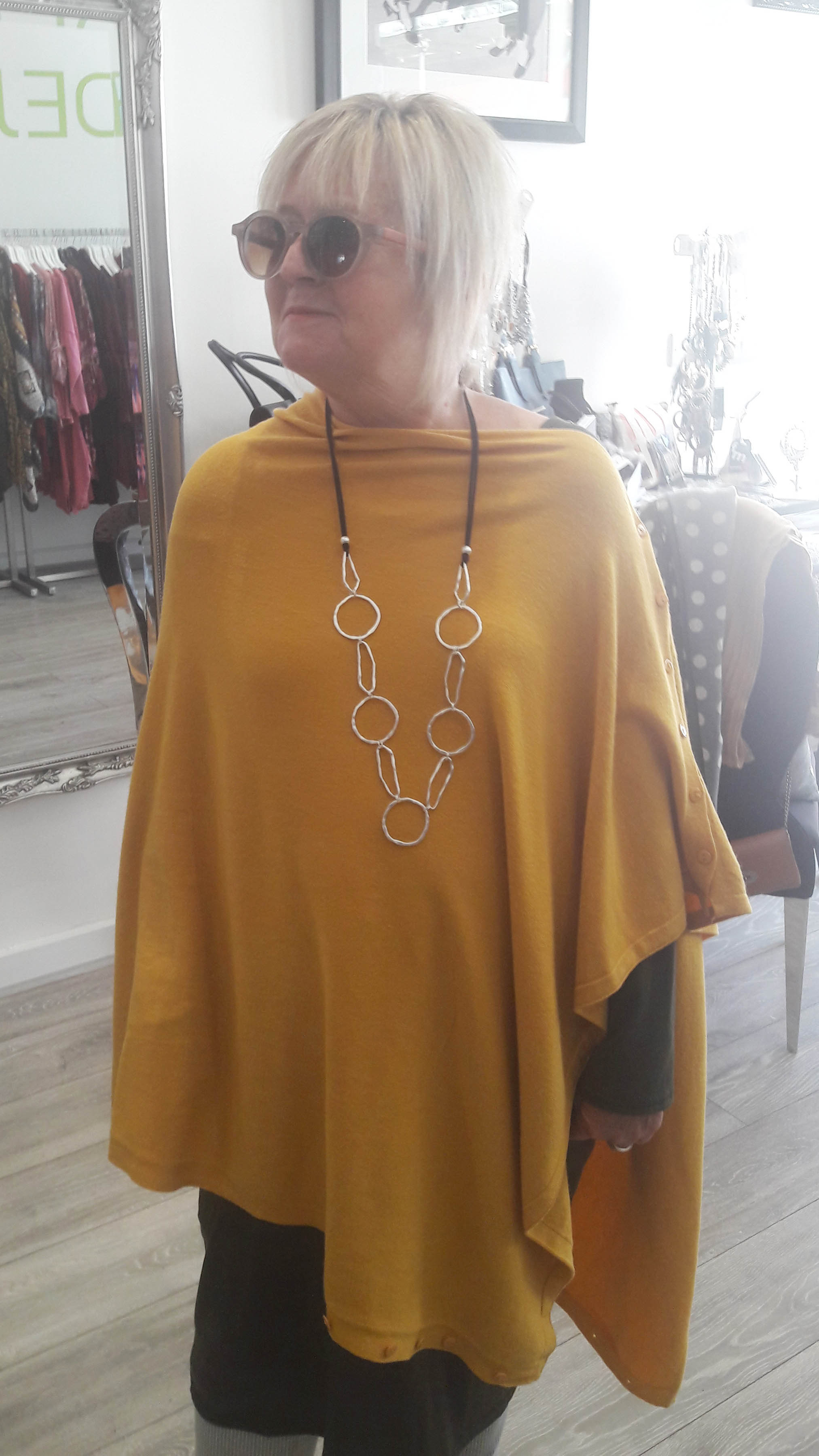 woman wearing mustard poncho and statement long silver necklace